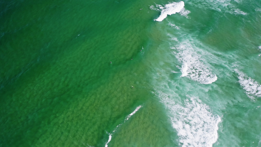 Aerial view of waves of emerald green ocean rolling towards the shore. Unrecognized surfer trying to cash perfect wave | Shutterstock HD Video #1057244779