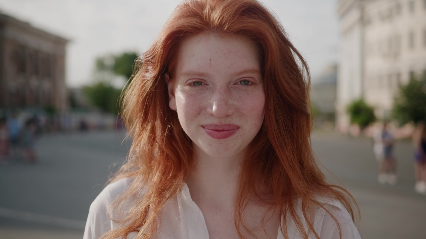 Face young sunshine woman with red hair look at camera smile stand in the city streets summer beautiful lady portrait happy outdoor close up slow motion | Shutterstock HD Video #1057244920