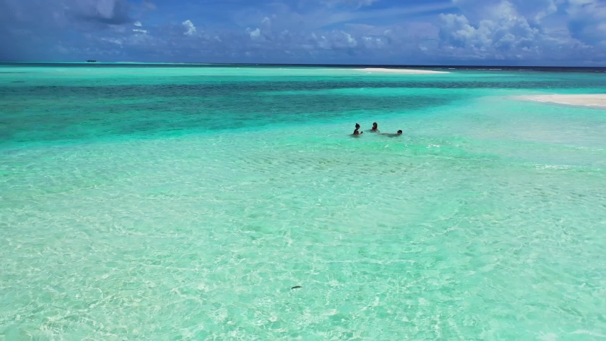 Wide aerial shot of three girls having fun together while they swim in slow motion in the shallow turquoise sea near the white sand shore, zooming in. | Shutterstock HD Video #1057245937