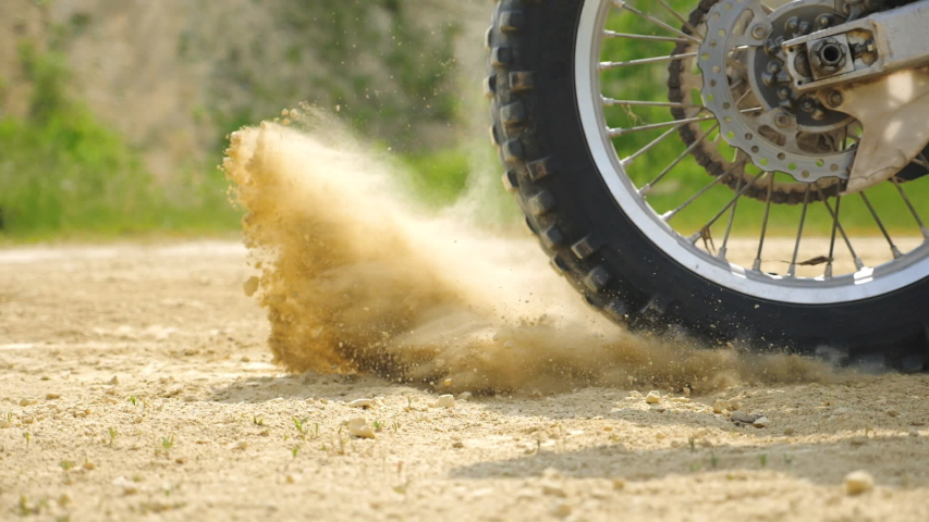 Close up wheel of powerful off-road motorcycle starting movement. Motocross bike starts move. Dry ground or dust flying around. Concept of motorsport or active lifestyle. Slow motion Side view | Shutterstock HD Video #1057247542