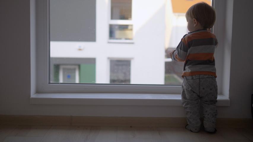 Little baby child look outside on window, waiting | Shutterstock HD Video #1057247869