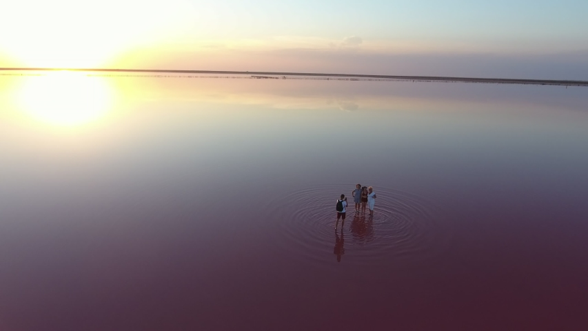 Inspiring bird`s eye view of a horizonless white sand shore with shallow waters and people taking photos at splendid sunset in summer. It looks nice and beautiful. | Shutterstock HD Video #1057249288