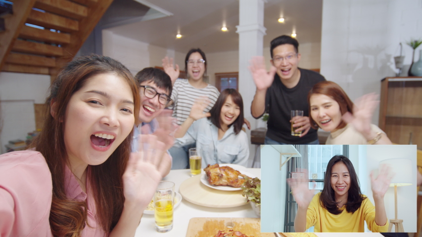 Group of young Asian people look at camera, remote video call greeting with friend at home dinner party. Point of view vlog or selfie camera. New normal lifestyle, social distancing concept Royalty-Free Stock Footage #1057251868