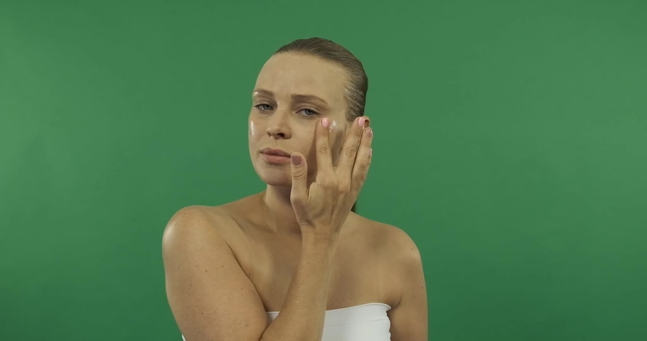 Woman applying cream to her face   Shutterstock HD Video #1057253842