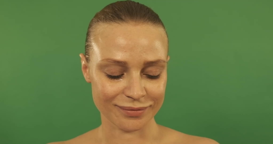 Woman applying cream to her face   Shutterstock HD Video #1057254082