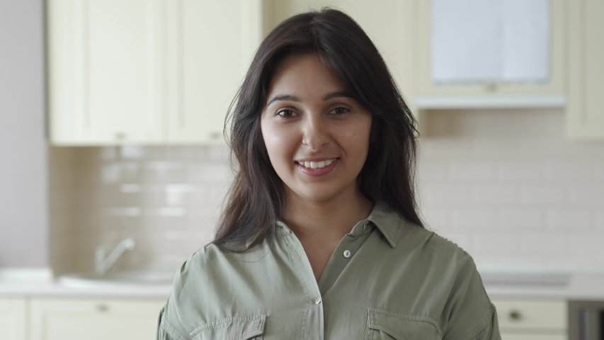 Smiling young pretty indian ethnicity woman looking at camera alone at home in kitchen. Happy beautiful millennial hindu lady housewife in India indoors, close up face front headshot portrait.