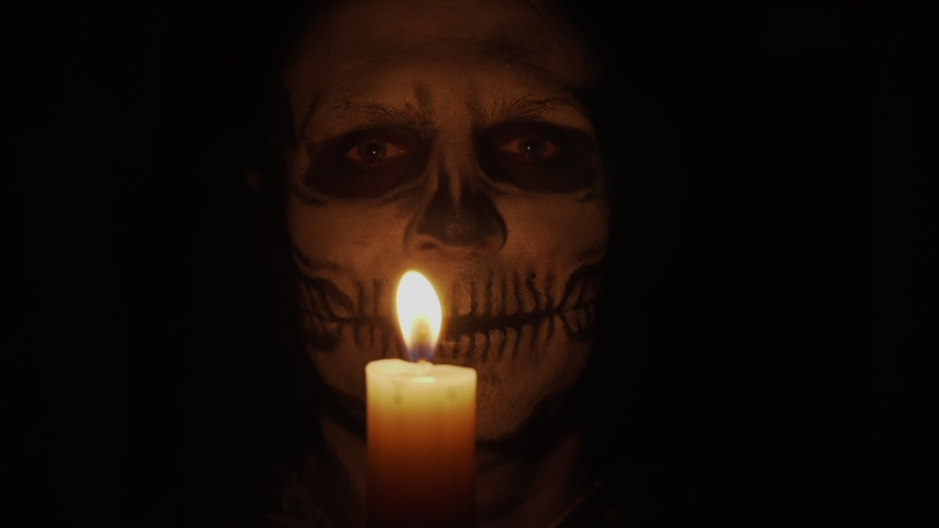 A man with skeleton makeup looks at the camera. A man smiles a creepy and funny smile. Skeleton in the dim light of a candle. Halloween and horror concept. Royalty-Free Stock Footage #1057255723