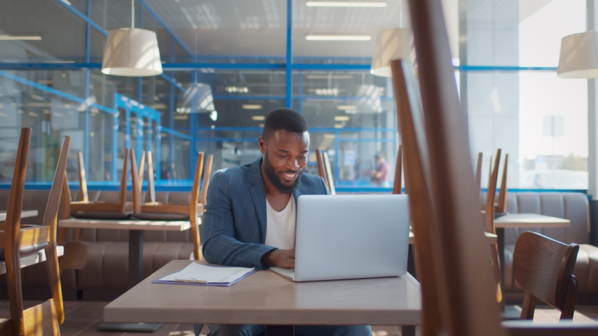 African young entrepreneur working on laptop preparing for opening cafe. Smiling afro-american coffee shop owner using laptop doing preparation for reopening after quarantine. Small business concept Royalty-Free Stock Footage #1057256413