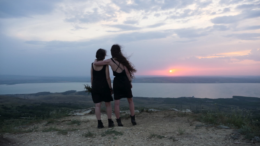 Two woman in black dresses stand on the mountain in summer against the background of the lake | Shutterstock HD Video #1057257313