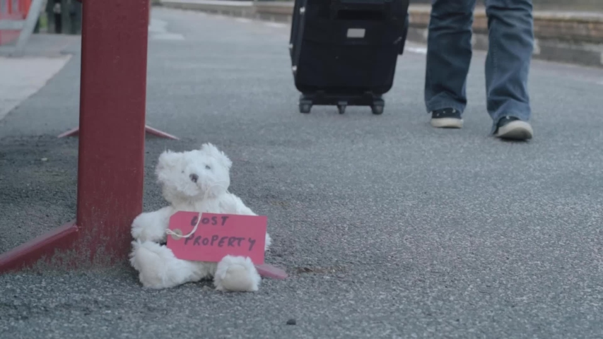 Teddy with lost property tag left on train platform as commuter goes by with suitcase | Shutterstock HD Video #1057257454