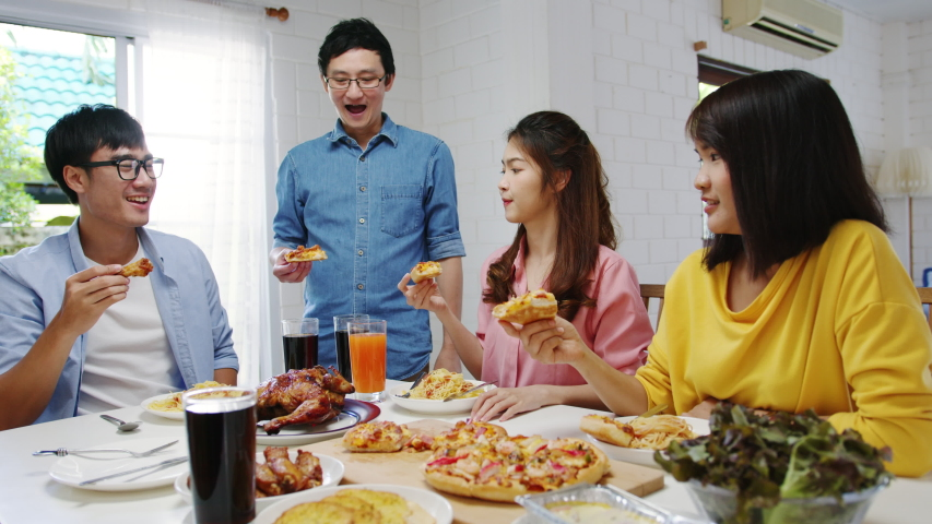 Happy young friends group having lunch at home. Asia family party eating pizza food and laughing enjoying meal while sitting at dining table together at house. Celebration holiday and togetherness. | Shutterstock HD Video #1057257703