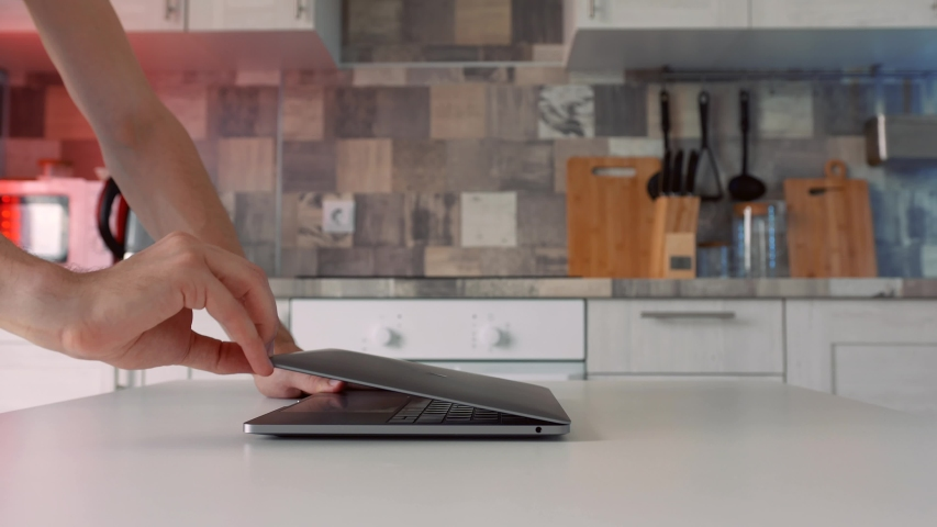 Concept of working at home during isolation. Action. Side view of male hands openning new silver laptop that is standing on the white table in the kitchen. Royalty-Free Stock Footage #1057257739