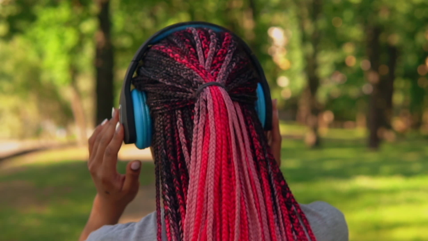 Rear view close up african american woman with headphones listening music on the street slow motion summer city with sunlight | Shutterstock HD Video #1057258000