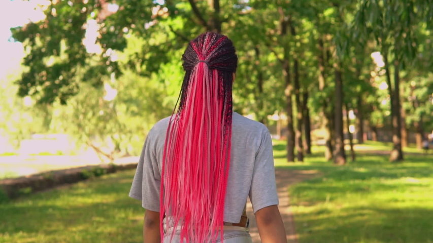 Back view african american woman with pink hairstyle strolling on the street slow motion summer landscape on background | Shutterstock HD Video #1057258087