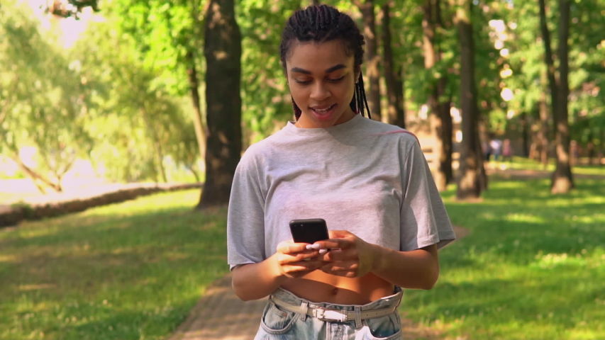 Front view african young student chatting online holding mobile looking at the camera cheerful smile walking on the street slow motion | Shutterstock HD Video #1057258093