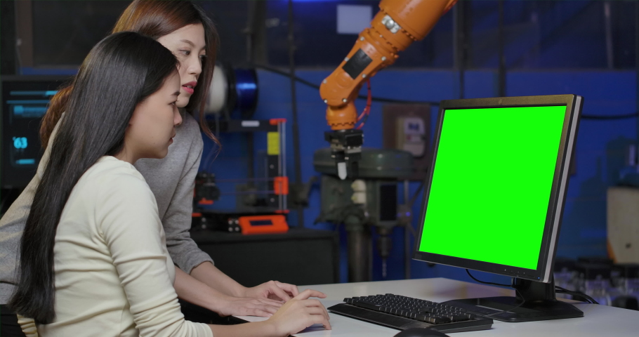 Team of Young Asian Female Industrial Robotics Engineer Using Computer With Green Screen to Test and Program Robot Arm at late night in Laboratory. People with technology or innovation concept.   Shutterstock HD Video #1057260349