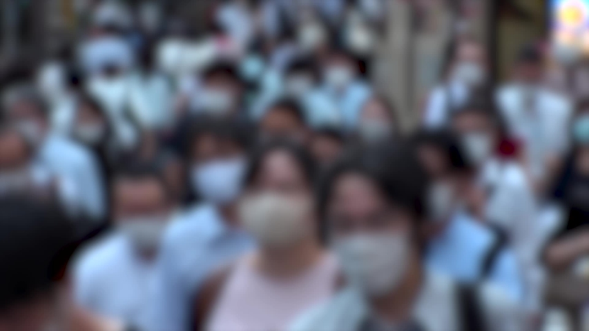 TOKYO, JAPAN - JUL 2020 : Crowd of people at the street near Shinjuku station in rush hour. Commuters wearing surgical mask to protect from Coronavirus (COVID-19) in hot summer. Blurred slow motion. | Shutterstock HD Video #1057260907