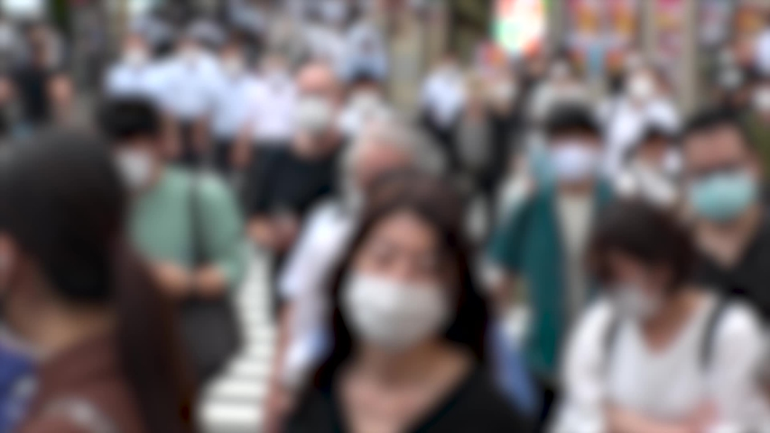 TOKYO, JAPAN - JUL 2020 : Crowd of people at the street near Shinjuku station in rush hour. Commuters wearing surgical mask to protect from Coronavirus (COVID-19) in hot summer. Blurred slow motion. | Shutterstock HD Video #1057260919