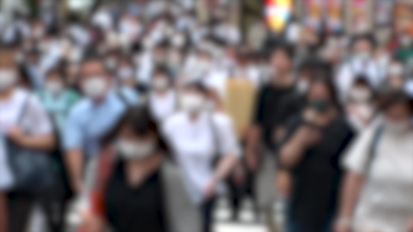 TOKYO, JAPAN - JUL 2020 : Crowd of people at the street near Shinjuku station in rush hour. Commuters wearing surgical mask to protect from Coronavirus (COVID-19) in hot summer. Blurred slow motion. | Shutterstock HD Video #1057260925