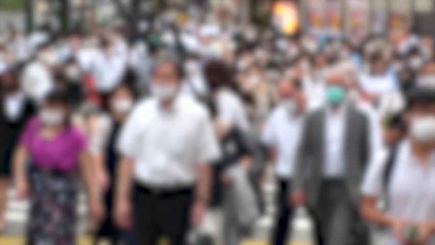 TOKYO, JAPAN - JUL 2020 : Crowd of people at the street near Shinjuku station in rush hour. Commuters wearing surgical mask to protect from Coronavirus (COVID-19) in hot summer. Blurred slow motion. | Shutterstock HD Video #1057260928