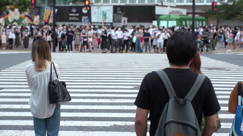 SHIBUYA, TOKYO, JAPAN - AUG 2020 : Crowd of people wearing surgical mask to protect from Coronavirus (COVID-19) at Shibuya Crossing. Shot in day time, hot summer season. Blurred slow motion. | Shutterstock HD Video #1057261003