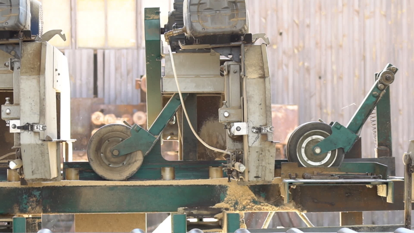 Sawing machine at wood production factory. Timber material processing and cutting at the sawmill. The manufacturing process at lumber mill. Automatic Circular Sawing Machine. | Shutterstock HD Video #1057264678