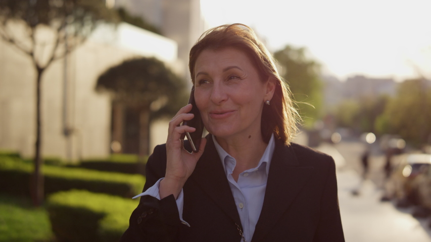 Portrait of an adult woman university teacher on the background of the educational institution talking on the phone. Mature girl teacher on the background of the school calls on a smartphone. High | Shutterstock HD Video #1057266544