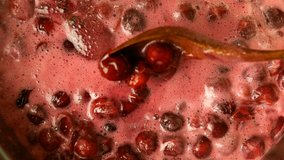 Homemade cooking. Video clip of active making cherry jam boiling process. Preparation of sweet cherry confiture and mixing it with wooden spoon. Top view, top down food.