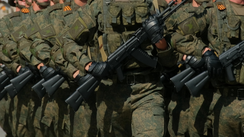 Parade military army soldiers with assault rifle ak-47 in hands march even formation closeup. Officers walk street hold in arm kalashnikov firearm 4K. Soldier marching show kalashnikov ak 47 close up.