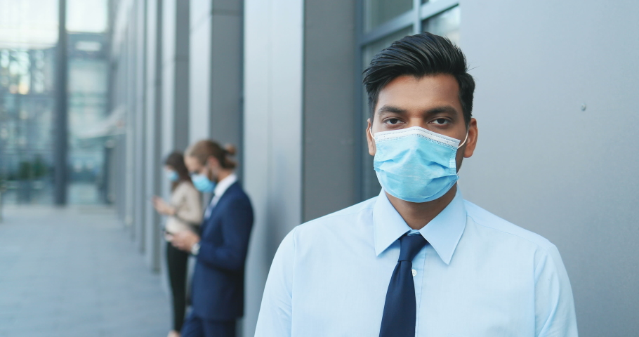 Portrait of Hindu young handsome businessman standing at street and looking at camera. Man from India in tie and medical mask outside business center. Social distance. Close up. Covid-19.   Shutterstock HD Video #1057273315