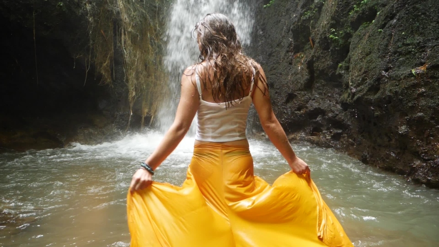 A young woman with long, dark hair is walking with her yellow pants / skirt into the water towards a small waterfall. Swinging and dancing with her body and arms to the sides.
