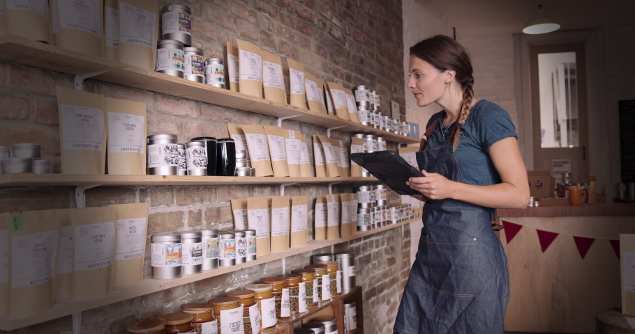 Female shop assistant taking shelf inventory in store using digital tablet with wireless technology Royalty-Free Stock Footage #1057278712