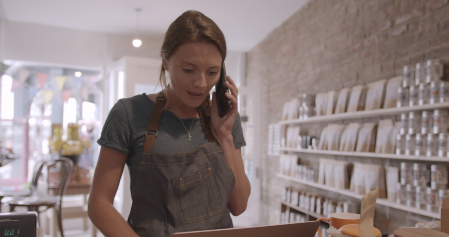 Female retail store owner calling customer and looking on laptop computer in shop, using smart phone, wireless technology Royalty-Free Stock Footage #1057278751