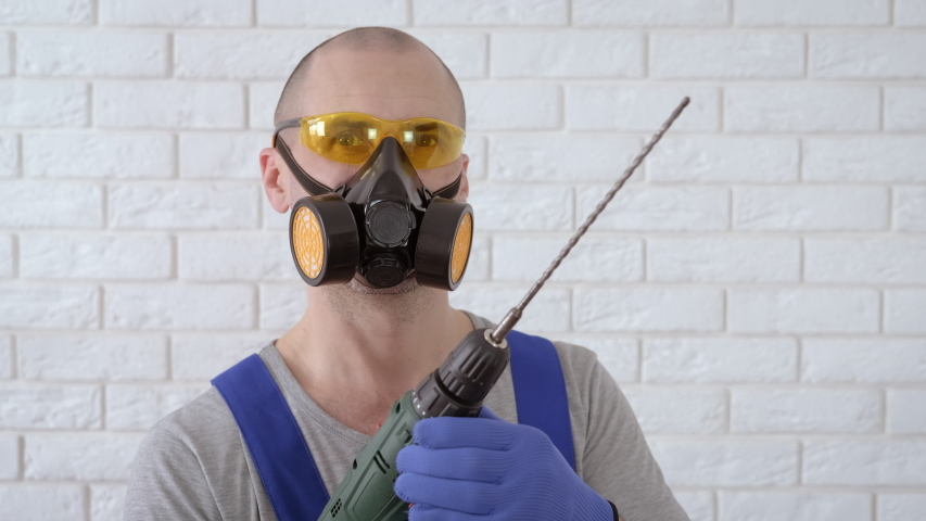 Builder with a drill. A man in a respirator wearing goggles with a drill. | Shutterstock HD Video #1057279045
