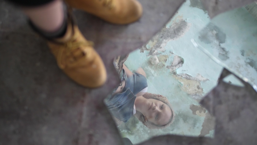 A young woman is smashing pieces of a mirror showing her own reflection with her boots on a dirty, dusty, concrete floor. Angry and furious with energy. Royalty-Free Stock Footage #1057283080