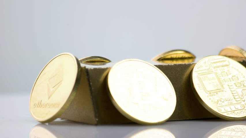 Stack of various cryptocurrency coins and gold bar. Close up of golden bitcoin, litecoin, ethereum, ripple XRP coins on gray background. Mining or blockchain technology. | Shutterstock HD Video #1057284235