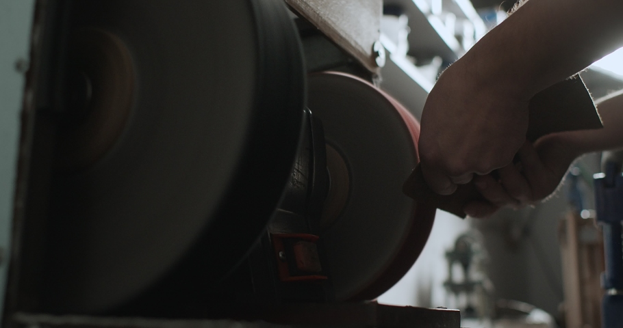 Close up view of the master grinds and polishes the edges of the leather to make them smooth. Male hands of craftsman working with leather and grinding wheel in 4k resolution in slow motion | Shutterstock HD Video #1057284625