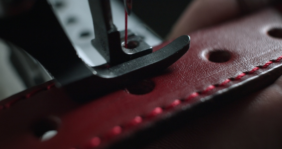 Close-up view of tailor works on sewing machine in private leather craftshop, stitching belt in process. male seamstress sewing leather belt in leather workshop in 4k slow motion | Shutterstock HD Video #1057284664