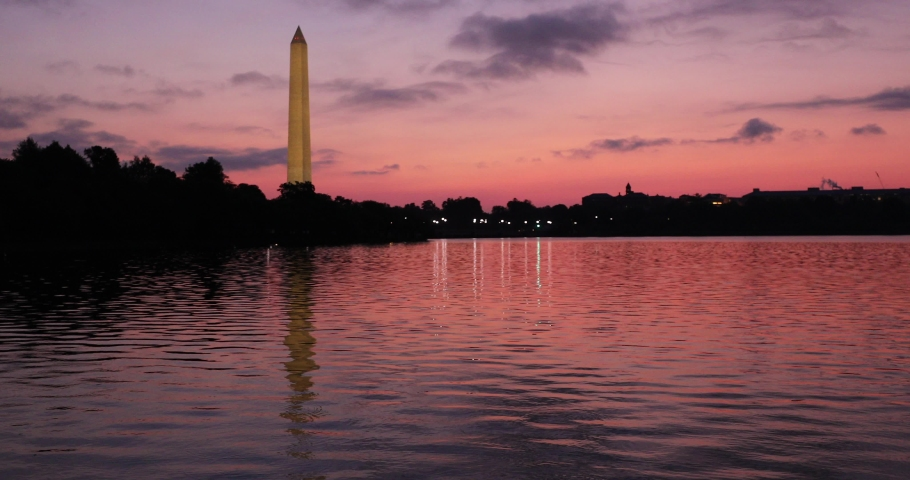 The sun rises behind the Washington Monument at the Tidal Basin on the National Mall.