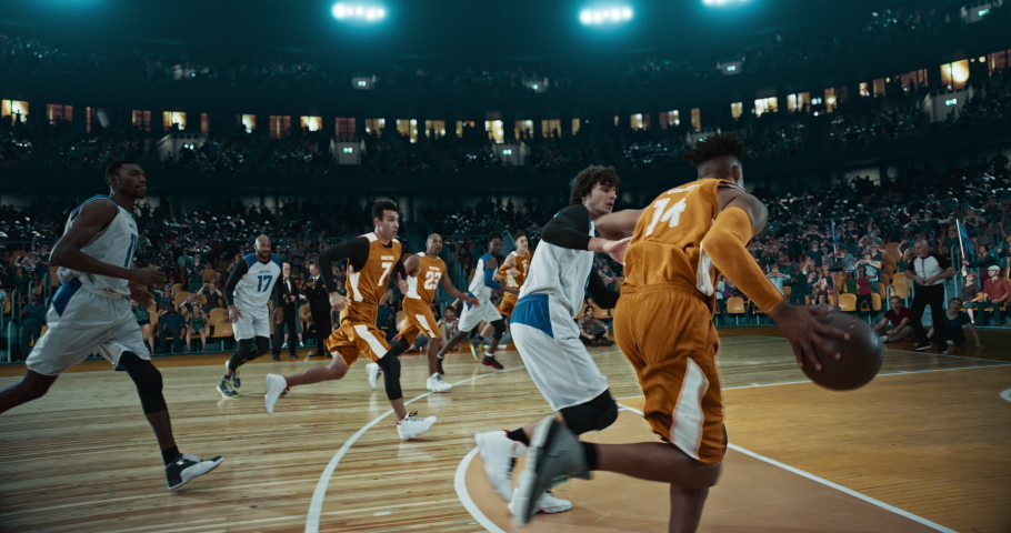 Basketball player scores a goal on a professional basketball stadium. Stadium is made in 3d with animated crowd. Dynamic shot.