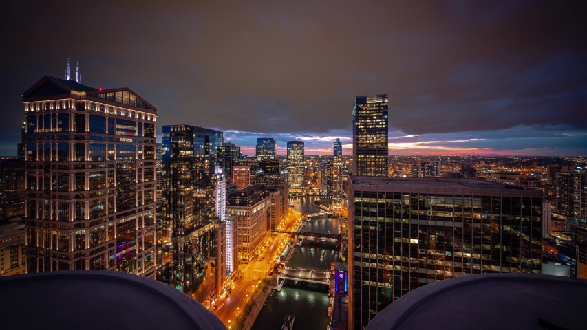 Beautiful aerial time lapse of downtown Chicago with boats on river passing bridges along Wacker Drive as sun sets below the horizon lighting up clouds and lights come on in the city at night.