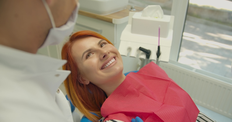 Confident smiling young adult european woman looking at camera standing at dental office. Happy millennial casual red-haired lady with white teeth pretty face posing for close up portrait indoors.