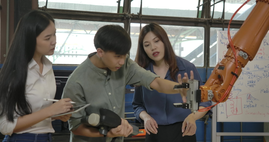 Team of Young Asian Industrial Robotics Engineer Working Testing and Program Robot Arm in a Research Laboratory with Modern Equipment together. People with technology or innovation concept.
