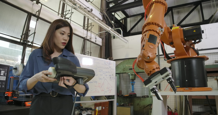 Young Asian Female Industrial Robotics Engineer is Testing and Program Robot Arm in a Research Laboratory with Modern Equipment. People with technology or innovation concept.
