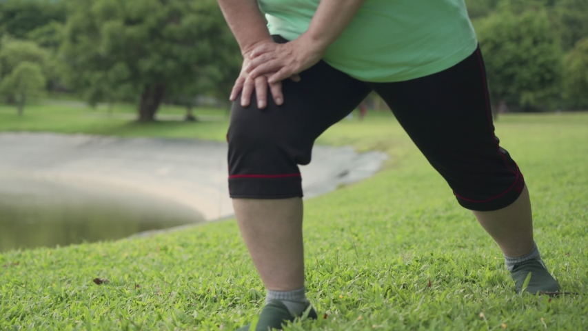 over weight female stretching her legs hand to Knee, standing legs stretch, cool down after morning exercise at the outdoor park, old age healthy life, lower body section, standing lunge practicing Royalty-Free Stock Footage #1057300510