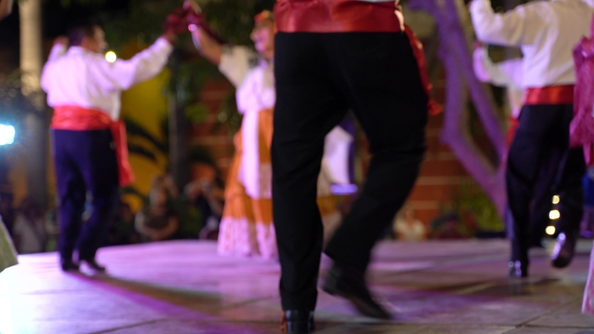 Shallow depth of field showing man and woman doing Mexican dance in background. Royalty-Free Stock Footage #1057300576