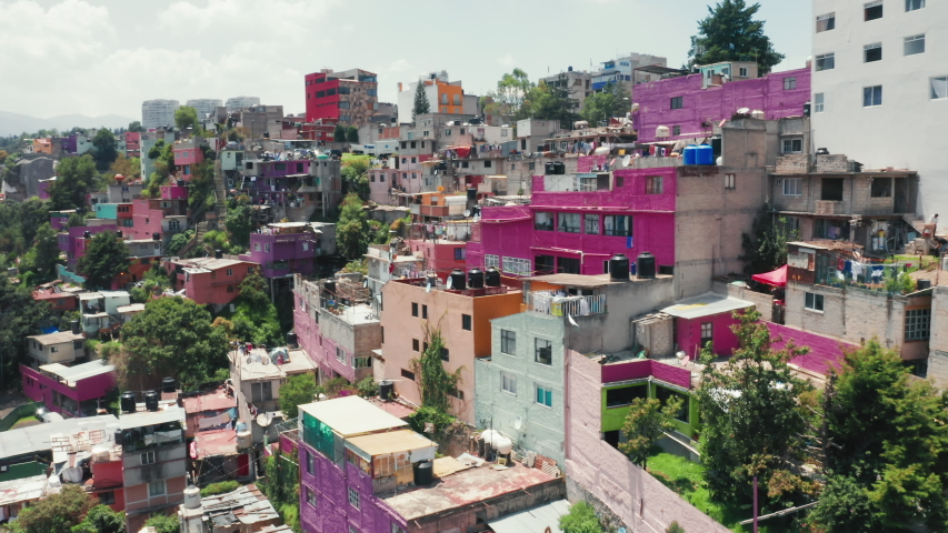Famous Mexico city destination site with pink favelas on the green hillside. Vibrant Mexico city suburban district. Traveling Central America, exploring Mexico city. Low-income buildings 4K aerial