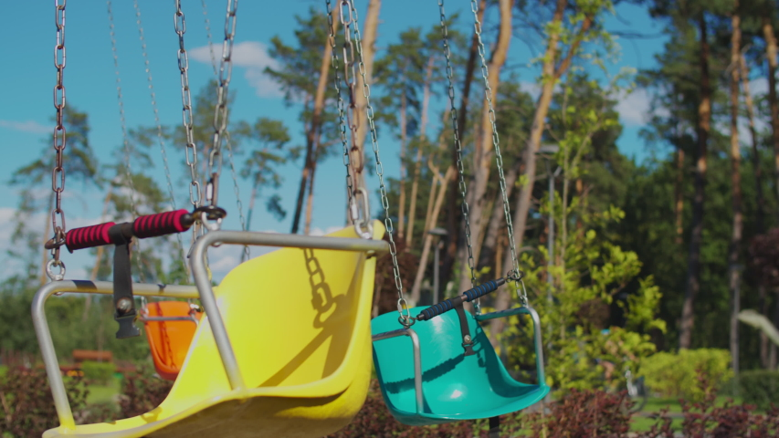 Two kids riding color chairoplane carousel in funfair. Siblings having fun alone in park. Social distance during quarantine.  Royalty-Free Stock Footage #1057305787