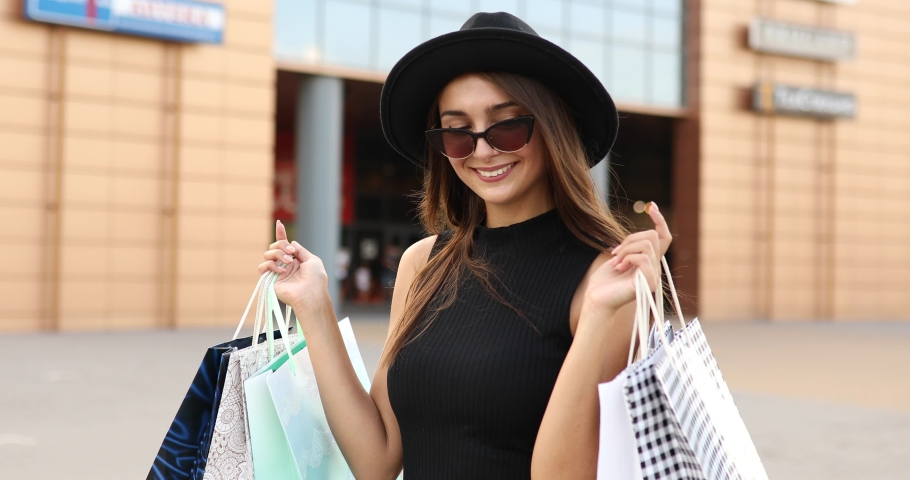 happy Shopaholic girl, in a black dress, black hat and sunglasses, Shopping, Black Friday Royalty-Free Stock Footage #1057306462