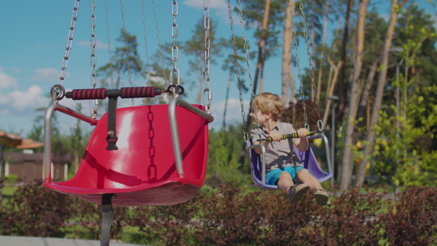 Two kids riding color chairoplane carousel in funfair. Siblings having fun alone in park. Social distance during quarantine.  Royalty-Free Stock Footage #1057310830